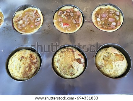 """Eggs that are seasoned and seasoned in a steel look like tray are  with the underneath of which is a stove which heats the cooked egg. Use the name """"egg hole"""" as a food sold at market or Street Food.  #694331833"""