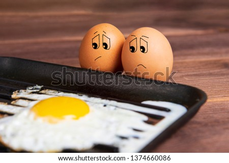 Eggs with a sad face near a fried egg. Humorous picture