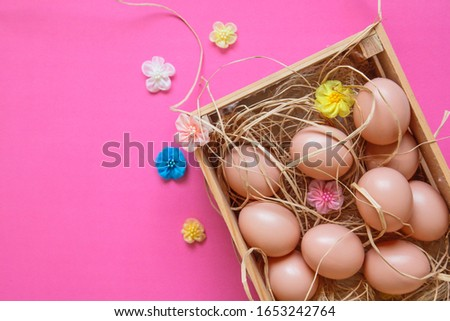 Eggs with flowers in the wooden box in the hay on the pink background. Easter concept. Healthy feeding concept.
