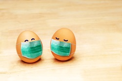 Eggs with smiling eyes and green medical or hygienic mask on wood background, Preparing for protection children from Covic 19 or Corona virus pestilence on Easter day concept