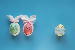 Eggs with smiling eyes and green medical or hygienic mask on wood background, Preparing for protection children from Covid 19 or Corona virus pestilence on Easter day concept