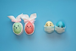 Eggs with smiling eyes and green medical or hygienic mask on wood background, Preparing for protection children from Corona virus pestilence on Easter day concept