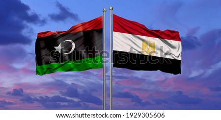 Egypt and Libya flag waving in the wind against white cloudy blue sky together. Diplomacy concept, international relations. Stockfoto ©