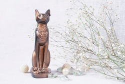 egypt cat statuette and flowers on light background