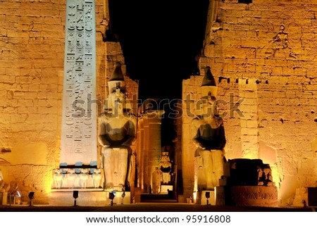 Egypt. Illuminated Luxor Temple. The red granite obelisk and two seated statues of Ramesses II in front of the first pylon