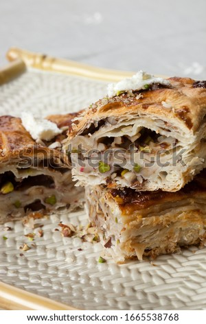 Egypt's famous dessert Om Ali, Umm Ali or Oum Ali slices and ingredients. Egyptian Bread Pudding. Arabic cuisine, Egypt culture concepts. Vertical close-up on white background. Stock photo ©