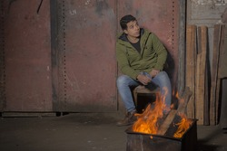 Egyptian Arabian Handsome and elegant young student sitting in front of the fire in Cairo at cold night in Egypt middle east, Africa