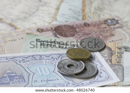 Egyptian coins and notes on map of Middle East, selective focus