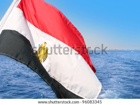Egyptian flag over the blue sea and sky background.