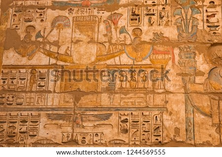 Egyptian hieroglyphs and drawings on the walls and columns. Egyptian language, The life of ancient gods and people in hieroglyphics and drawings #1244569555