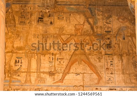Egyptian hieroglyphs and drawings on the walls and columns. Egyptian language, The life of ancient gods and people in hieroglyphics and drawings #1244569561