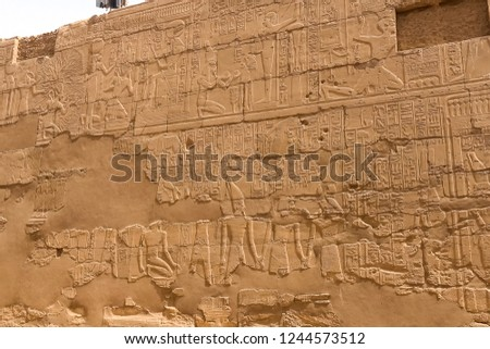Egyptian hieroglyphs and drawings on the walls and columns. Egyptian language, The life of ancient gods and people in hieroglyphics and drawings #1244573512