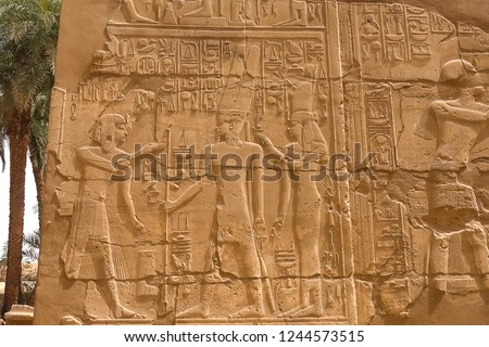 Egyptian hieroglyphs and drawings on the walls and columns. Egyptian language, The life of ancient gods and people in hieroglyphics and drawings #1244573515