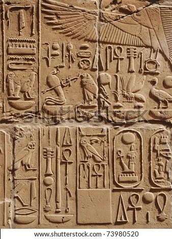 Egyptian images and hieroglyphs engraved on stone in Horus temple, Edfu, Egypt