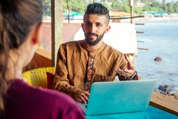 Egyptian man foreign language teacher teaching female student at tropical cafe