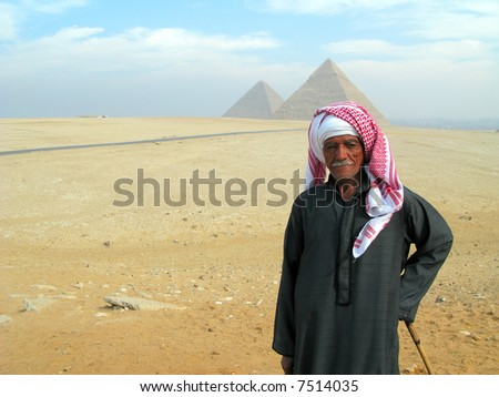 Egyptian man in traditional dress with the Great Pyramids in the distance in Cairo, Egypt. - stock photo