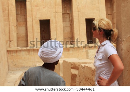 Egyptian man showing tourist woman Egyptian temple, Egypt