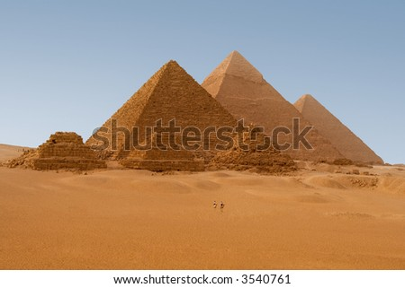Egyptian pyramids in Giza. 2 policemen on their camels provide visual clue about how gigantic these pyramids are.