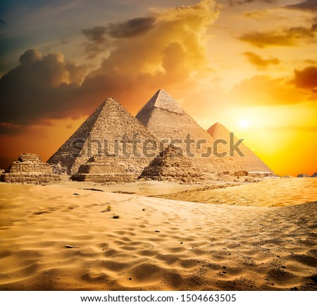 Egyptian pyramids in the desert at sunset