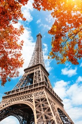 Eiffel Tower against the blue sky and autumn trees in Paris, France. Famous travel destination