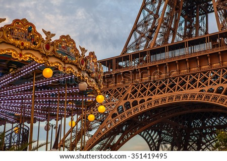 Stock Photo Eiffel tower and carousel in Paris against dramatic twilight sky at evening summer time.