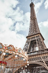 Eiffel Tower and carousel on background of clouds and blue sky. Paris, France.