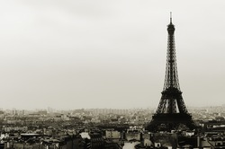 Eiffel tower and Paris roofs view on cloudy day in black and white