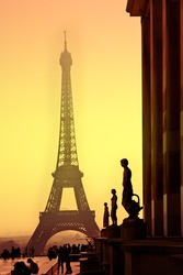 Eiffel Tower and silhouettes of sculptures. View from the Trocadero. Sanset.