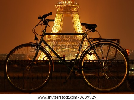 Eiffel tower at night and a bicycle in front of it in Paris