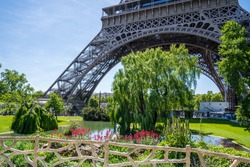 Eiffel Tower blue sky and green park or city view with many details in spring or summer with flowers, picturesque and romantic