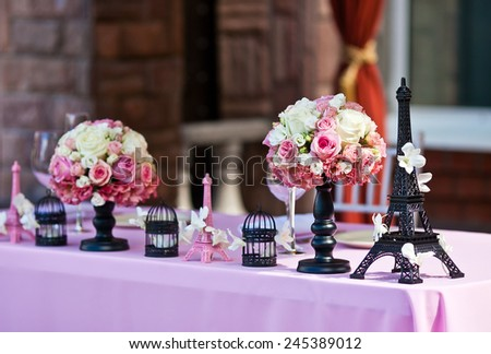Eiffel tower figurine on a wedding table with white petals, flower bouquets and bird cages on a pink tablecloth. Flowers on a background