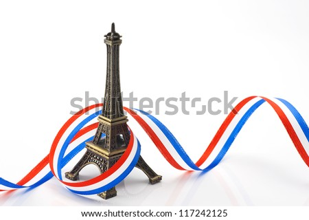 eiffel tower figurines with ribbon on white background