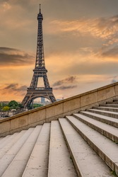 Eiffel Tower in Paris Europe at sunrise photographed from the Trocadero steps with lead in lines and orange background