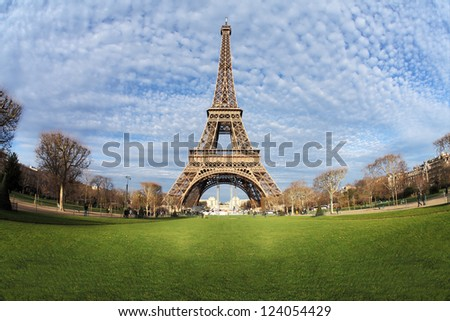 Eiffel Tower in Paris with green grass, blue sky and white clouds