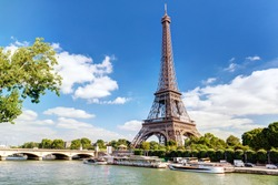 Eiffel tower in summer, Paris, France. Scenic panorama of the river Seine under the blue sky. Nice scenery of the city.