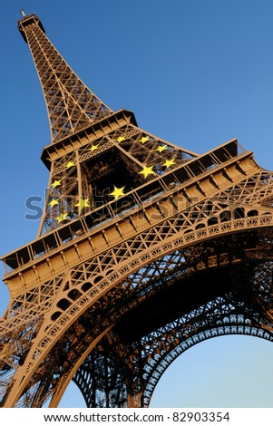 Eiffel Tower lit by golden sunlight against clear blue sky, displaying the European Union Circle of Stars symbol on the front.  The photo was taken tilted at an angle for dramatic effect.