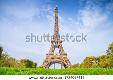 Eiffel Tower on blue sky background in summer sunny day. View on Eiffel tower from Mars fields without tourists. Sunny Paris cityscape.