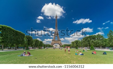Eiffel Tower on Champs de Mars in Paris timelapse hyperlapse, France. Blue cloudy sky at summer day with green lawn and people walking around