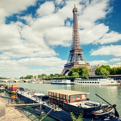 Eiffel tower on Seine river, Paris, France. Scenic view of Paris in summer. Residential barges and tourist boats on the Seine in Paris center. Traveling and vacation in Paris. Instagram style photo.