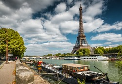 Eiffel tower on the River Seine, Paris, France. Scenic panorama of Paris city with residential barges. Beautiful view of the embankment of Seine in Paris center. Cityscape of Paris in summer.