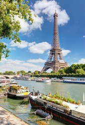 Eiffel tower on the river Seine, Paris, France. Scenic view of Seine with residential barges and tourist boats in Paris center. Beautiful scenery of Paris city in summer. Sunny Paris postcard.