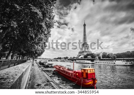 Eiffel Tower over Seine river in Paris, France. Red tourist ship on water. Vintage, black and white. #344855954