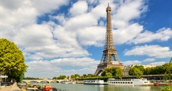 Eiffel tower over Seine River, Paris, France. Majestic Eiffel tower is one of the main landmarks in Europe. Scenery of Eiffel Tour in summer. Panoramic view of the city with the Eiffel construction.