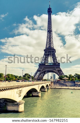 Eiffel tower, Paris, France. Majestic Eiffel tower on the river Seine in summer. Vintage photo of Paris with an old bridge and the main great landmark against sky. Cityscape of Paris on a sunny day.