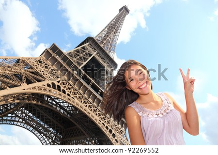Eiffel Tower tourist posing smiling by Eiffel Tower Paris France during Europe travel trip Young happy excited multiracial Asian Caucasian woman in her 20s
