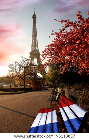 Eiffel Tower with french flag on bench during a spring time in Paris, France