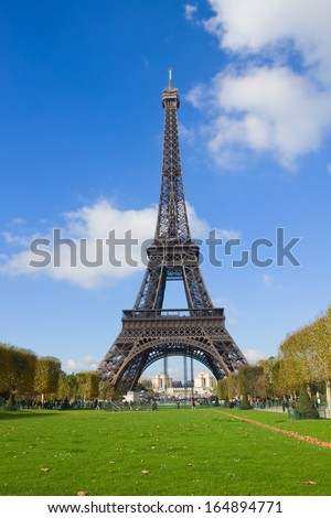 Eiffel Tower with green lawn in sunny day in Paris France