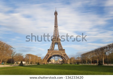 Eiffel tower with moving clouds on blue sky, Paris