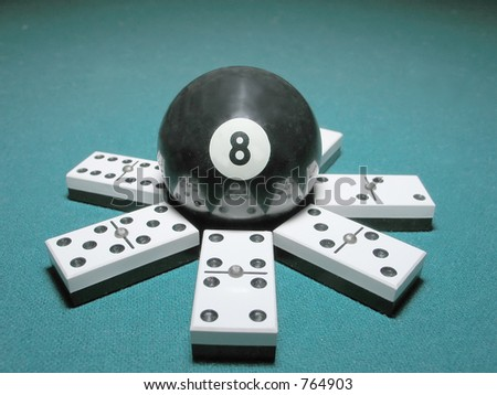 Eight ball from billiard game on top of a seven domino double structure.