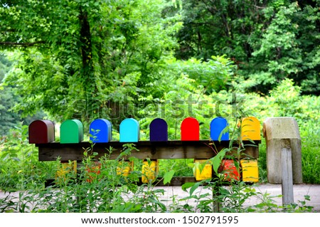 Eight brightly colored mailboxes sit besides each other on a wooden rail.  They are surrounded by bright green foliage. #1502791595